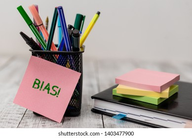 Handwriting text Bias. Concept meaning inclination or prejudice for or against one demonstrating group Writing equipment and note paper sheets with agenda book on the wooden desk.