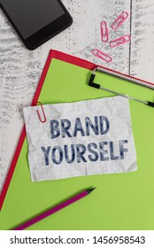 Handwriting text Brand Yourself. Concept meaning Develop a unique professional identity Personal product Clipboard paper sheet pencil smartphone note clips wooden retro background.