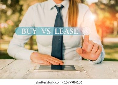 Handwriting text Buy Vs Lease. Concept meaning Own something versus borrow it Advantages Disadvantages Female business person sitting by table and holding mobile phone.