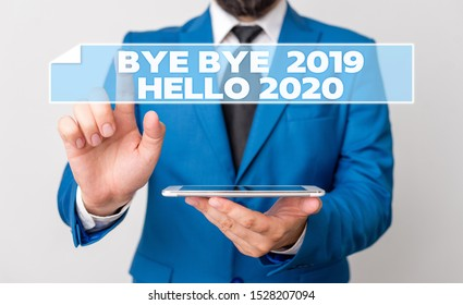 Handwriting text Bye Bye 2019 Hello 2020. Concept meaning Starting new year Motivational message 2019 is over Businessman with pointing finger in front of him.