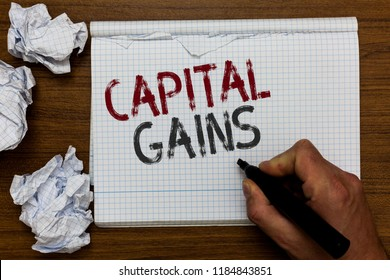 Handwriting text Capital Gains. Concept meaning Bonds Shares Stocks Profit Income Tax Investment Funds Man holding marker notebook crumpled papers ripped pages mistakes made.