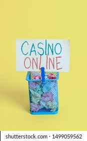 Handwriting text Casino Online. Concept meaning Computer Poker Game Gamble Royal Bet Lotto High Stakes Trash bin crumpled paper clothespin empty reminder office supplies yellow.