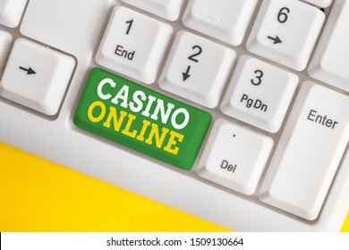 Handwriting text Casino Online. Concept meaning Computer Poker Game Gamble Royal Bet Lotto High Stakes White pc keyboard with empty note paper above white background key copy space.