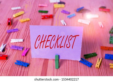 Handwriting text Checklist. Concept meaning List down of the detailed activity as guide of doing something Colored clothespin papers empty reminder wooden floor background office.
