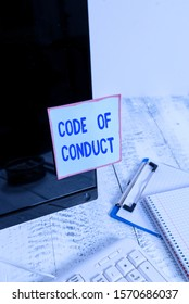 Handwriting text Code Of Conduct. Concept meaning Ethics rules moral codes ethical principles values respect Note paper taped to black computer screen near keyboard and stationary.
