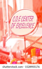 Handwriting text Coe Center Of Excellence. Concept meaning being alpha leader in your position Achieve Round shape mirror and toiletries placed next to sink in a modern bathroom.
