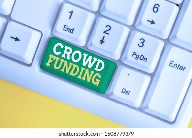 Handwriting text Crowd Funding. Concept meaning Fundraising Kickstarter Startup Pledge Platform Donations White pc keyboard with empty note paper above white background key copy space.