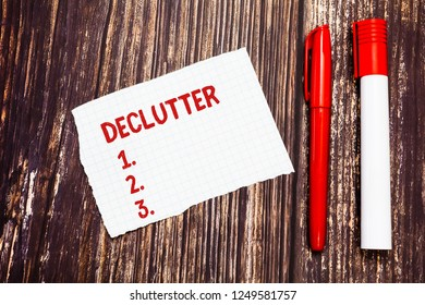 Handwriting text Declutter. Concept meaning remove unnecessary items from untidy or overcrowded place Blank Torn Index sized Graph Paper Two Pens for Writing on Wood Surface.