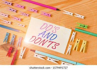 Handwriting text Do S And Don Ts. Concept meaning Technologically complication of making a decision Colored clothespin papers empty reminder wooden floor background office.