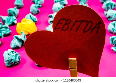 Handwriting text Ebitda. Concept meaning Earnings Before Interest Taxes Depreciation Amortization Abbreviation Clothespin holding red heart paper crumpled papers ideas mistakes trials.