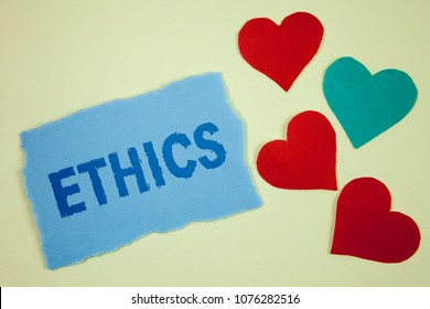 Handwriting text Ethics. Concept meaning Maintaining equality balance among others having moral principles written on Tear sticky note paper piece on plain background paper Hearts next to it.
