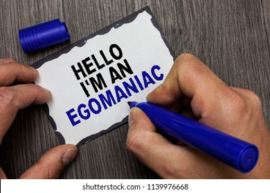 Handwriting text Hello I am An Egomaniac. Concept meaning Selfish Egocentric Narcissist Self-centered Ego Gray wooden deck hand hold black marker written black lined sticky note.