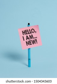 Handwriting text Hello I Am New. Concept meaning used greeting or begin telephone conversation Ballpoint blank colored sticky note peaceful cool pastel fashion background.