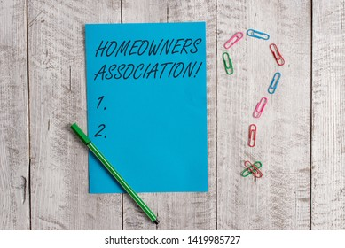 Handwriting text Homeowners Association. Concept meaning Organization with fee for upkeeps of Gated Community Pastel colour note paper placed next to stationary above the wooden table.