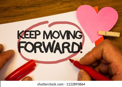 Handwriting text Keep Moving Forward Motivational Call. Concept meaning Optimism Progress Persevere Move Human hand retain red pen circled black words paper hook rivet pink heart.