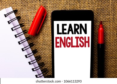 Handwriting text Learn English. Concept meaning Study another Language Learn Something Foreign Communication written on Mobile Phone on the jute background Marker and Notebook next to it.