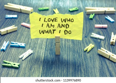 Handwriting text I Love Who I Am And What I Do. Concept meaning High self-stem being comfortable with your job Paperclip hold written torn page many clips laid on bluish wooden floor.