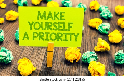 Handwriting text Make Yourself A Priority. Concept meaning Think in your own good first personal development Paperclip retain written words yellow paper paper lobs laid on wooden floor.