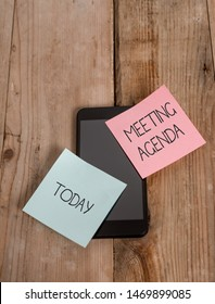 Handwriting text Meeting Agenda. Concept meaning An agenda sets clear expectations for what needs to a meeting Smartphone two colored sticky notes lying vintage old wooden background.