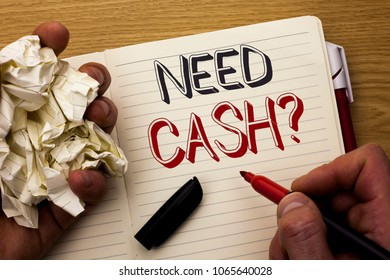 Handwriting text Need Cash Question. Concept meaning Wealth Question Needy Currency Money Advice Conceptual written by Man on Notebook Book Holding Marker on the wooden background Pen next to it.