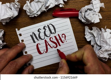 Handwriting text Need Cash question. Concept meaning asking someone if you need extra money or dont Man holding marker notebook page crumpled papers several tries mistakes.