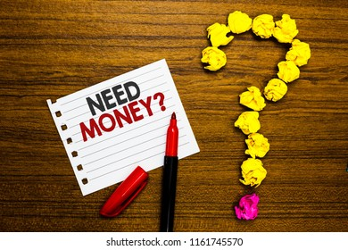 Handwriting text Need Money question. Concept meaning asking someone if he needs cash or bouns Get loan Paper marker crumpled papers forming question mark wooden background.