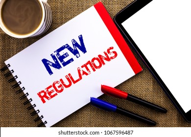Handwriting text New Regulations. Concept meaning Change of Laws Rules Corporate Standards Specifications written on Notebook Book on the jute background Tablet Coffee Cup and Pens next to it.