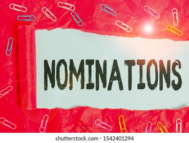 Handwriting text Nominations. Concept meaning action of nominating or state being nominated for prize Paper clip and torn cardboard placed above a plain pastel table backdrop.