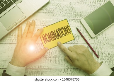 Handwriting text Nominations. Concept meaning action of nominating or state being nominated for prize Hand hold note paper near writing equipment and modern smartphone device.