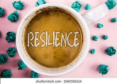 Handwriting text Resilience. Concept meaning Capacity to recover quickly from difficulties Persistence written on Coffee in White Cup within Crumpled Paper Balls on plain pink background.