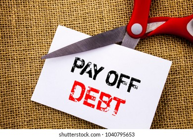 Handwriting text showing Pay Off Debt. Conceptual photo Reminder To Paying Owed Financial Credit Loan Bills written Sticky Note Paper Cutting by Scissors the textured background