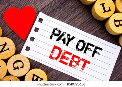 Handwriting text showing Pay Off Debt. Conceptual photo Reminder To Paying Owed Financial Credit Loan Bills written tear note paper sticky note the wooden background with heart.