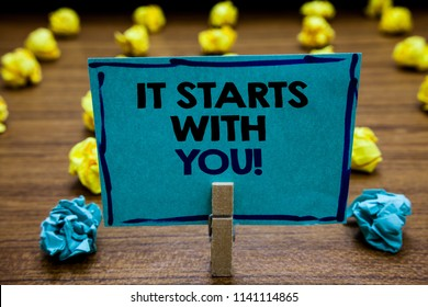 Handwriting text It Starts With You. Concept meaning Motivation for starting doing something Have discipline Blurry wooden deck yellow and blue lob on ground paper clip grip page with text.