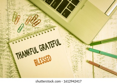 Handwriting text Thankful Grateful Blessed. Concept meaning Appreciation gratitude good mood attitude Slim metallic laptop blank spiral notepad pens clips lying wooden table.