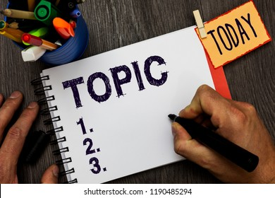 Handwriting text Topic. Concept meaning matter dealt with in text discourse or conversation subject News Man holding marker notebook clothespin hold reminder cup markers wood table.