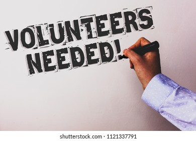 Handwriting text Volunteers Needed Motivational Call. Concept meaning Social Community Charity Volunteerism Advisors hand holding black marker whiteboard written black color words.