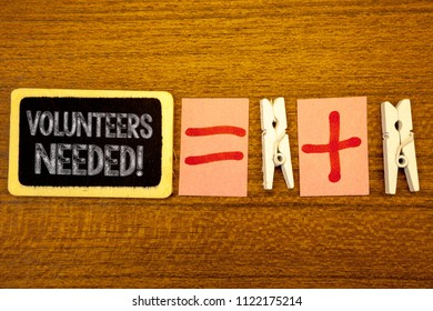 Handwriting text Volunteers Needed Motivational Call. Concept meaning Social Community Charity Volunteerism White paper clip laid woody desk black slate some texts equal and plus mark.