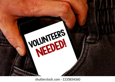 Handwriting text Volunteers Needed Motivational Call. Concept meaning Social Community Charity Volunteerism Brown jeans back pocket hand pushing mobile phone with black and red text.