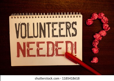 Handwriting text Volunteers Needed Motivational Call. Concept meaning Social Community Charity Volunteerism Reddish paper balls structures question mark red pen notebook browny desk.