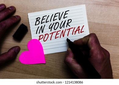 Handwriting text writing Believe In Your Potential. Concept meaning Have self-confidence motiavate inspire yourself Written on notepad hand hold marker with love heart wooden background.