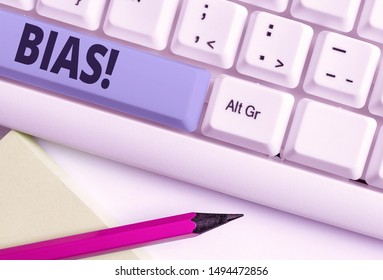 Handwriting text writing Bias. Concept meaning inclination or prejudice for or against one demonstrating group White pc keyboard with empty note paper above white background key copy space.
