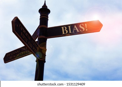Handwriting text writing Bias. Concept meaning inclination or prejudice for or against one demonstrating group Road sign on the crossroads with blue cloudy sky in the background.