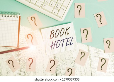 Handwriting text writing Book Hotel. Concept meaning an arrangement you make to have a hotel room or accommodation Writing tools, computer stuff and math book sheet on top of wooden table.
