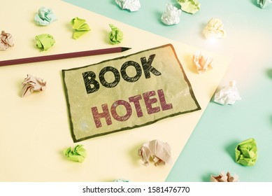 Handwriting text writing Book Hotel. Concept meaning an arrangement you make to have a hotel room or accommodation Colored crumpled papers empty reminder blue yellow background clothespin.