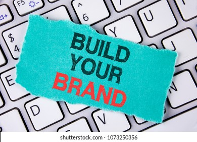 Handwriting text writing Build Your Brand. Concept meaning create your own logo slogan Model Advertising E Marketing written on tear Sticky Note Paper placed on the Laptop.