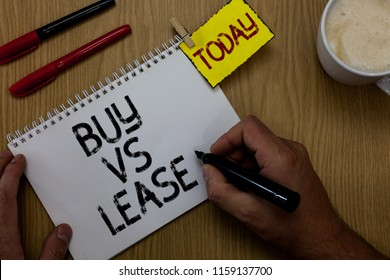 Handwriting text writing Buy Vs Lease. Concept meaning Own something versus borrow it Advantages Disadvantages Man holding marker notebook clothespin reminder wooden table cup coffee.