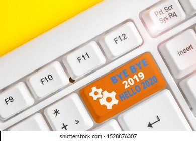 Handwriting text writing Bye Bye 2019 Hello 2020. Concept meaning Starting new year Motivational message 2019 is over White pc keyboard with empty note paper above white background key copy space.