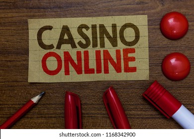 Handwriting text writing Casino Online. Concept meaning Computer Poker Game Gamble Royal Bet Lotto High Stakes Paperboard markers pencil wooden background communicating ideas red balls.
