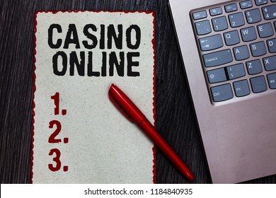 Handwriting text writing Casino Online. Concept meaning Computer Poker Game Gamble Royal Bet Lotto High Stakes Piece paper red borders black marker computer keyboard wooden background.