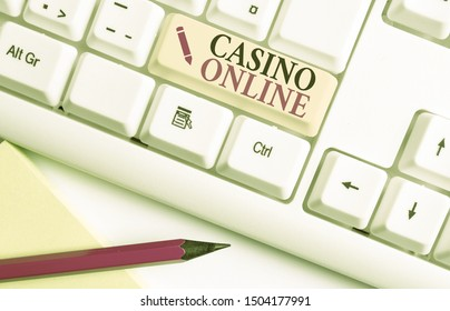 Handwriting text writing Casino Online. Concept meaning Computer Poker Game Gamble Royal Bet Lotto High Stakes White pc keyboard with empty note paper above white background key copy space.